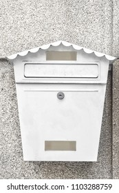 Close-up of white metal mailbox in shape of house hanging on gray textured wall.