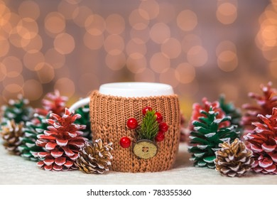 Closeup of  white mug isolated at holiday blurry lights background. One cute cup in knitted brown holder decorated with christmas details. Horizontal color photography.