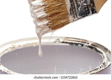 closeup of white paint dripping from the brush into a tin