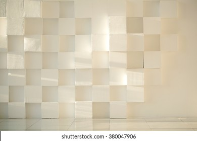 Close-up of white painted concrete modern wall made of cubes with tiled floor