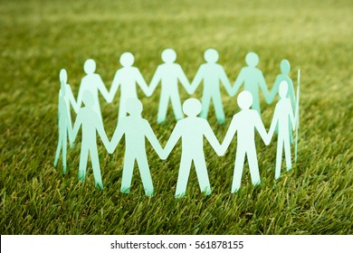 Close-up Of White Papercut Of People Chain On Grass