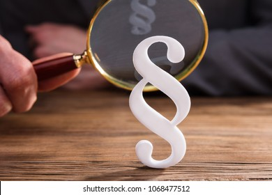 Close-up Of White Paragraph Symbol In Front Of Businessperson's Hand Holding Magnifying Glass