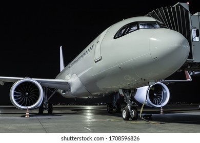 Close-up a white passenger aircraft at the jetway on an airport night apron