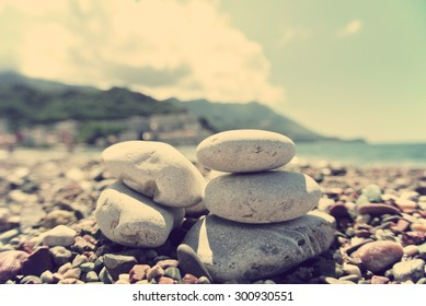 Closeup of white pebbles on the beach, on a sunny summer day. Image and edited in faded, washed out, retro, Instagram style with sepia filter; summer vintage concept.