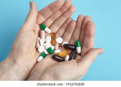 Closeup of white pils and colorful capsules on a hands.