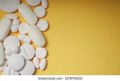 closeup of white pils on yellow background