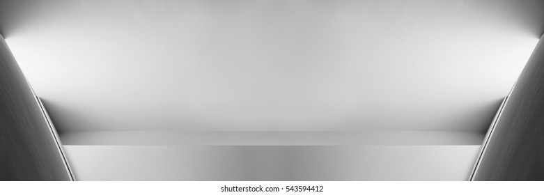 Close-up of white plastered wall with niche and spot light under pitched ceiling. Abstract black and white architectural background in minimalism style. Modern architecture. Building interior detail.