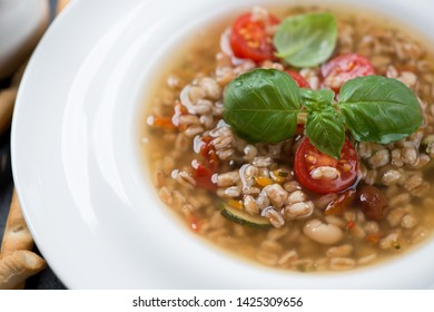Closeup of a white plate with italian spelt and minestrone soup, selective focus