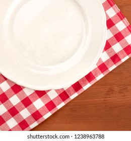 A closeup of a white plate on a vichy patter cloth on a dark rustic wooden table with copy space