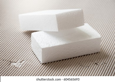 Closeup white polystyrene foam on corrugated paper. Polystyrene foam is cushioning material in packaging, material for craft applications and other.
