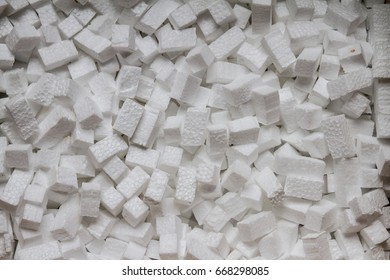 Closeup white polystyrene foam, styrofoam popcorn or packing noodles used to cushion the contents of packages while shipping that are commonly made of expanded polystyrene foam