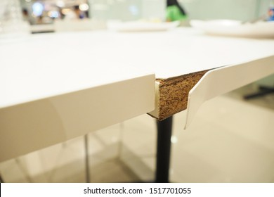 Closeup of white pvc sheets peeled off from the edge of dining table after using for years. Furniture usage wooden structure and lamination concept