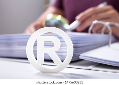 Close-up Of White Registered Trademark Sign Near Documents Over Desk