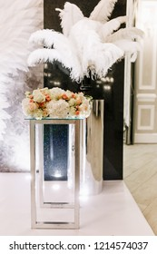 Close-up of white roses and black ostrich feather luxury wedding decor.