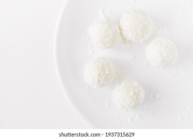 Close-up white round coconut candy on a white background. Empty space for text. Flat lay top-down
