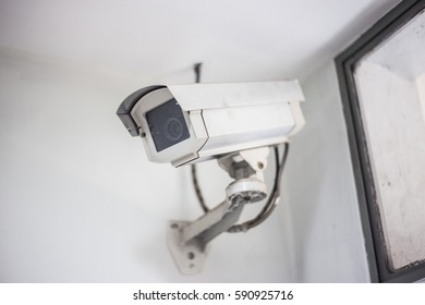 Closeup white security CCTV camera in office building