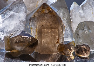 Close-up of white and smoky quartz stone crystals on dark granite polished slab. Group of quartz and rauchtopaz crystals as a background. Texture of quartz crystals.