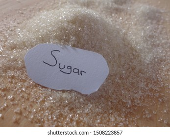 Close-up of white sugar and white paper with sugar name on the wood