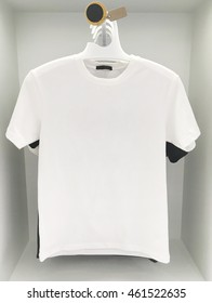 Closeup white T - shirt at the hanger in white wood wardrobe for sell