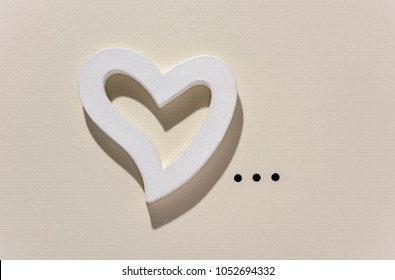 closeup of a white three-dimensional heart and points of ellipsis on an off-white background, with some blank space around them