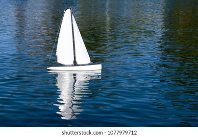 Closeup of a White Toy Sailboat on a Blue Pond