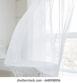 Closeup of white waving curtain in bedroom with window