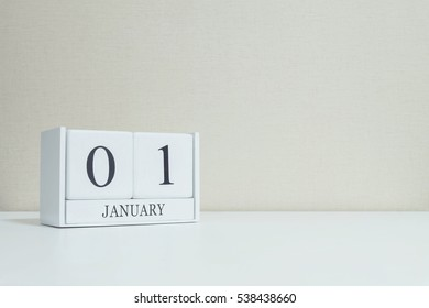 Closeup white wooden calendar with black 1 january word on blurred white wood desk and cream color wallpaper in room textured background with copy space , selective focus at the calendar