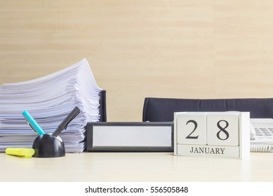 Closeup white wooden calendar with black 28 january word on blurred brown wood desk and wood wall textured background in office room view with copy space , selective focus at the calendar