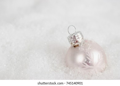 Close-up of white xmas ball under snowflakes in snow. Christmas and New Year concept with copy space. Christmas greeting card.