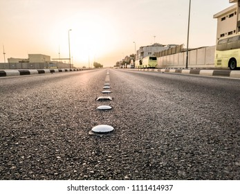 closeup of whits cat eyes or road reflectors on an empty street in a city and sunrise in the background