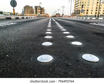 closeup of whits cat eyes or road reflectors on an empty street in a city with buildings and street lights in the background in a cloudy day