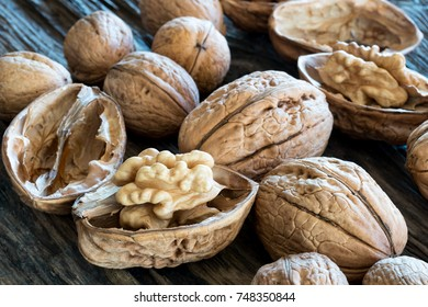 Closeup of whole and broken walnuts on a wooden background