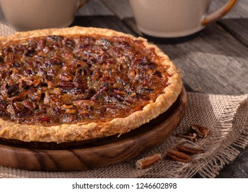 Closeup of a whole pecan pie with coffee cups in background on a rustic wooden surface