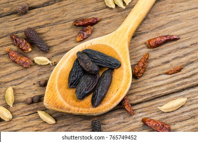 Closeup of whole tonka beans on an old wooden wooden spoon on rustic wood background with copy space