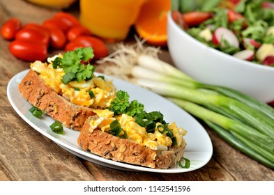 Close-up of wholemeal bread with scrambled eggs, fresh herbs, spring onions, tomatoes and salad bowl in background - healthy breakfast