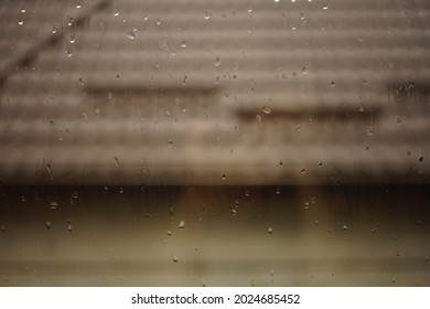Closeup window glass in rain drops. House with brown tiled roof in blurred background.
