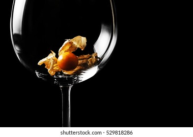Close-up of wine glass with physalis on black background