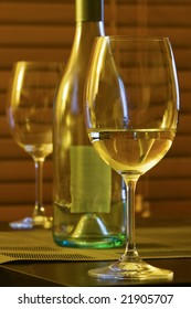 A closeup of wine glasses and bottle