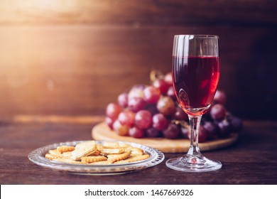 Close-up of a wine glasses with bread in communion plate  over grape on the wood plate against window light  on wooden table, christian background with copy space