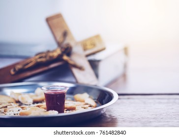 Close-up of a wine glasses  with bread in communion plate with blurred of crucifix of Jesus on the bible, christian background with copy space