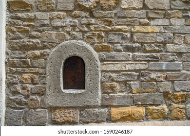 Close-up of a wine window (buchetta del vino), used in the past to sell wine directly to passers-by, on the old stone wall of an ancient building in the historic centre of Florence, Tuscany, Italy - Shutterstock ID 1590246187