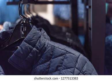Close-up winter down on clothes rack at American outdoor clothing shop. Insulated fashionable jacket with zip pocket.