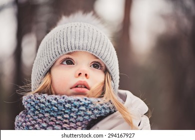 closeup winter portrait of adorable baby girl looking up in knitted hat and scarf