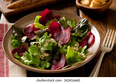 Closeup of a winter salad with beets and toasted pecan nuts.