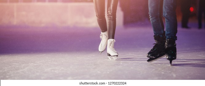 Closeup of winter skates on transparent ice rink night. Couple in love.