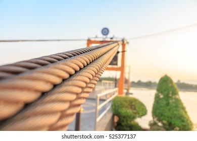 Closeup of wire or sling cable holding Suspension bridge across a river.Selective Focus on Center.