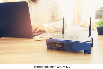 closeup of a wireless router and a man using Laptop and notebook computers on living room at home ofiice