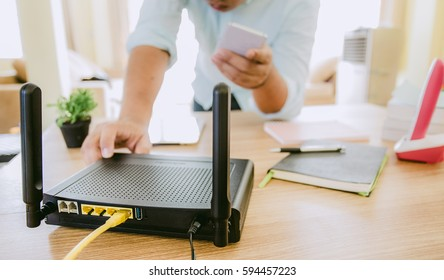 closeup of a wireless router and a man using smart-phone on living room at home ofiice