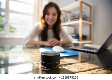 Close-up Of Wireless Speaker In Front Of Businesswoman Listening To Music