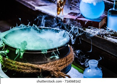 Closeup of witcher cauldron with blue potions for Halloween